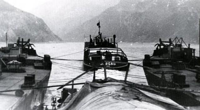 Casco tumbado y a los lados las barcazas que lo sujetan, delante un remolcador