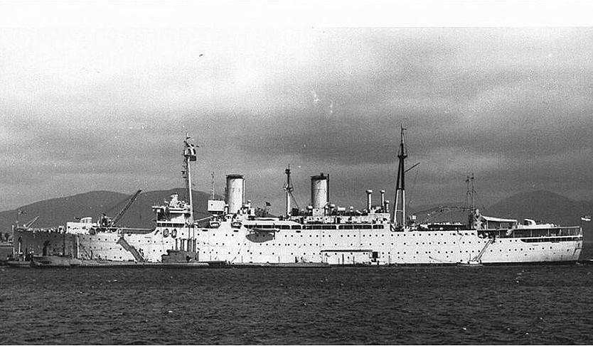 El HMS Montclare transformado en buque depósito de submarinos, a proa y popa se ven los antiaéreos de 4 pulgadas. Hay un sumergible abarloado a babor