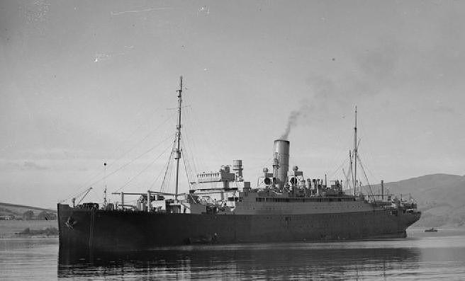El HMS Aurania tras su transformación en crucero auxiliar, se pueden apreciar los cañones en cubierta, los cambios en la pintura y que se han eliminado la mayoría de botes salvavidas. Tras el puente se ve lo que parece una antena de radar
